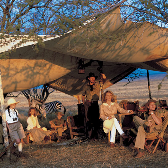 Models sitting under tent in Africa on safari with zebra