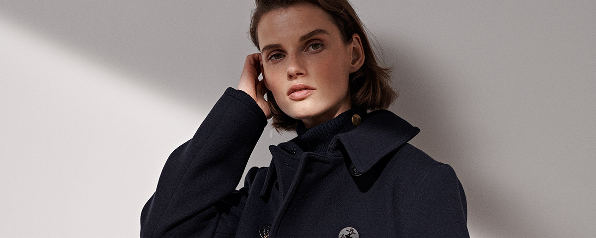 Woman in peacoat with anchor buttons
