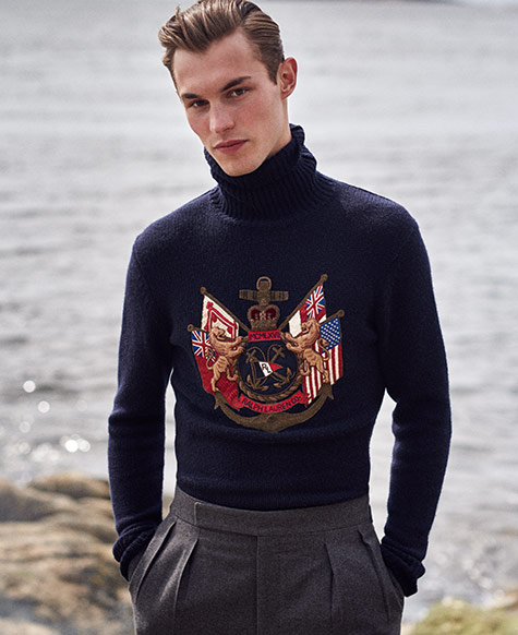 Man in navy turtleneck sweater with intricate flag-inspired crest embroidery