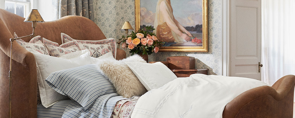 Photograph of bed made with linens in white, stripes, and floral patterns.