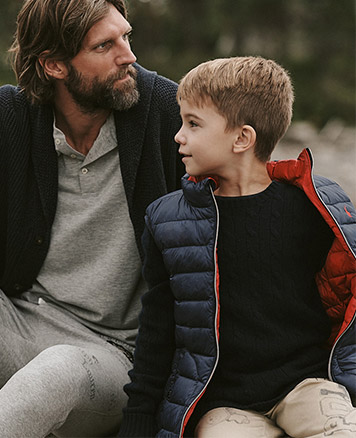 Boy wears puff vest over cable-knit sweater; man wears shawl sweater and grey outfit.