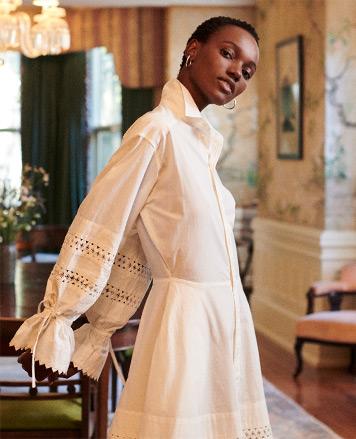 Woman in blouson-sleeve white eyelet dress