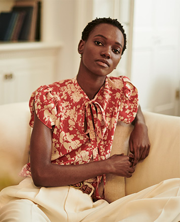 Woman in tie-neck short-sleeve red blouse with floral print